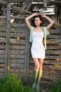Asian woman  posing near a tobacco drying shed  wearing a white dress and green wellies