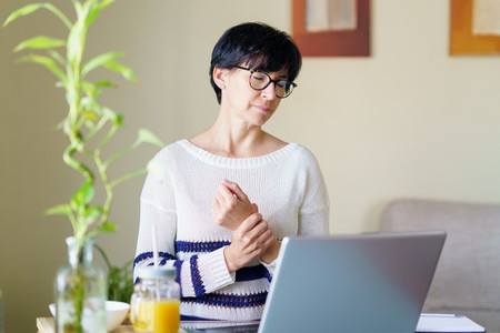 Woman teleworking from home with wrist pain having a massage to rest