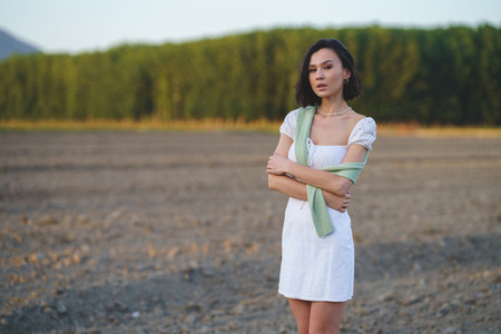 Asian woman  walking in the countryside  wearing a white dress