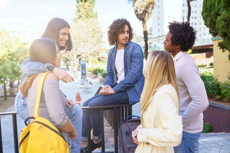 Multi ethnic group of students talking in the street