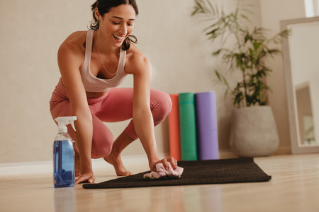 Woman disinfecting workout mat in gym