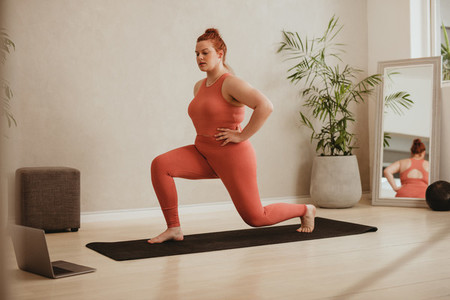Woman exercising over online workout class
