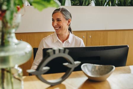 Smiling receptionist working on front desk