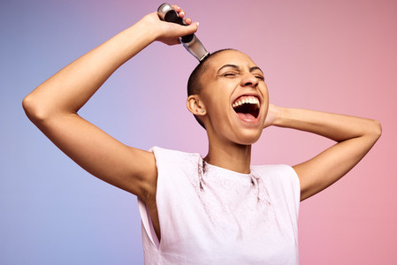 Bold female shaving off her head and laughing