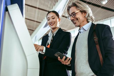 Flight attendant assisting man