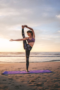 Young woman practicing yoga at beach
