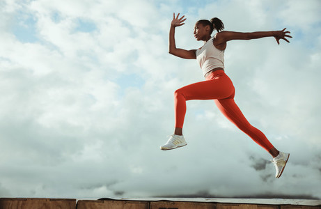 Female athlete in sportswear lunging and jumping midair