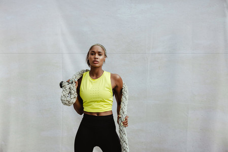 Sportswoman doing battle rope workout
