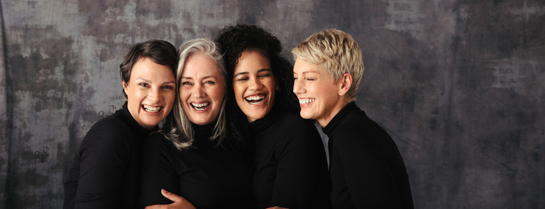Smiling women of different ages standing in a studio