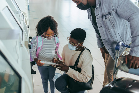 African family at airport looking boarding pass