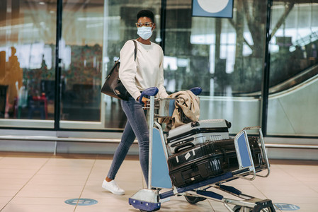 Woman traveler in face mask with luggage trolley at airport
