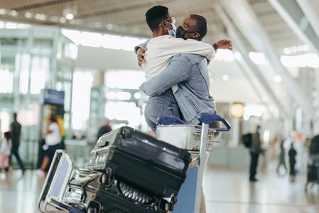 Man hugging woman at airport terminal