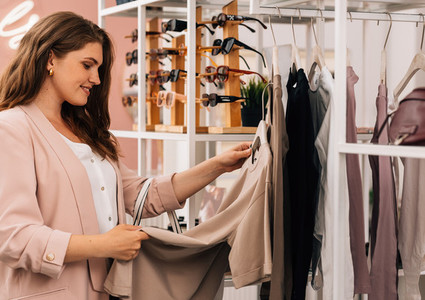 Side view of a smiling plus size woman shopping in a small clothing store