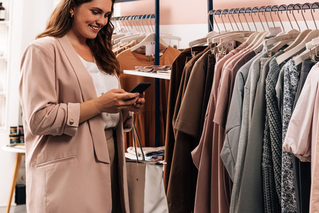 Smiling woman using cell phone while standing at a rack in a clothing store  Plus size female holding smartphone while shopping