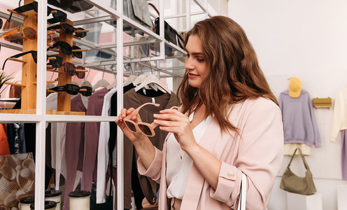 Elegant woman holding fashionable sunglasses while standing in small clothing shop