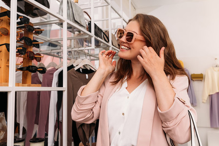 Smiling stylish woman wearing sunglasses in a fashion store