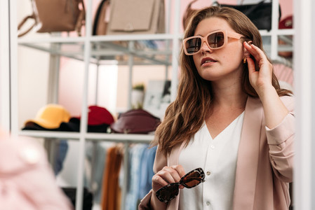 Beautiful plus size woman try on sunglasses in front of a mirror in a boutique  Young female choosing eyewear in store