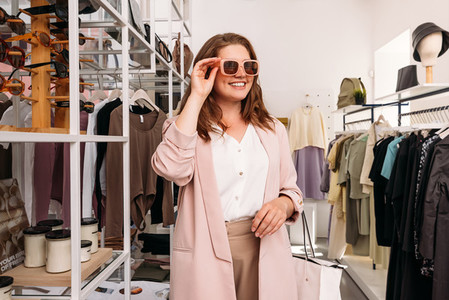 Happy plus size woman standing in small fashion store  Cheerful female buyer wearing sunglasses in a boutique