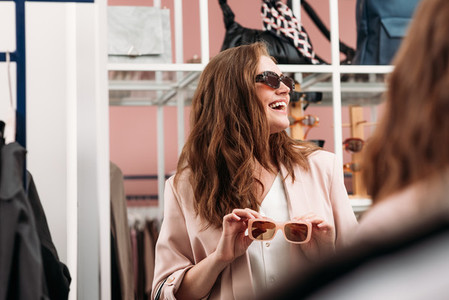 Happy woman looking away while choosing sunglasses in a fashion store in front of a mirror