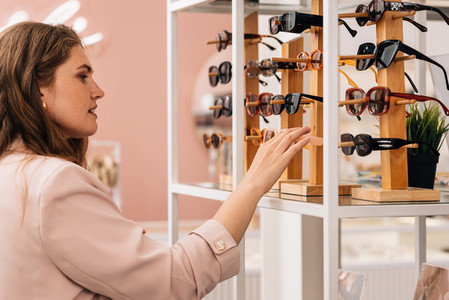 Side view of a young woman looking at rack with sunglasses in fashion store