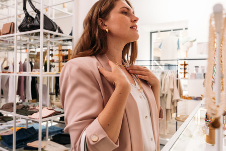 Side view of stylish woman try on a necklace in a small fashion store