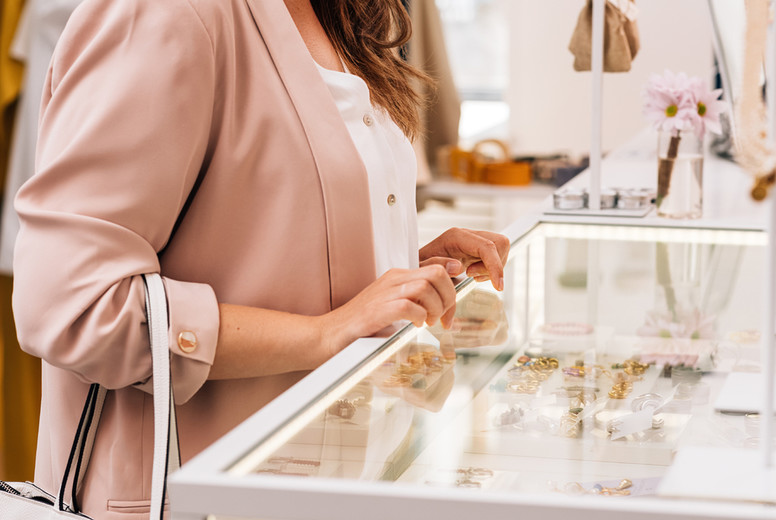 Young stylish woman choosing accessories in boutique  Elegant female buyer looking on display case with bijouterie