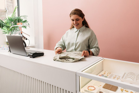 Saleswoman arranging clothes on a counter in store  Clothing store owner working at a table
