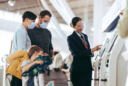Airport staff helping family with self check in