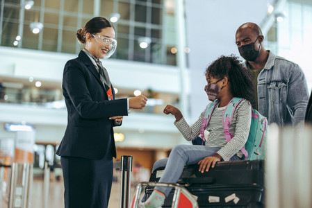 Airport attendant greeting small girl with family