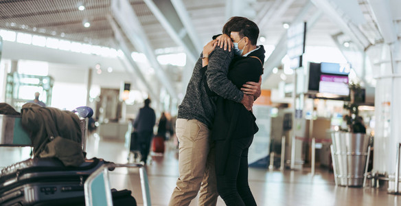 Man hugging woman after arriving from trip at airport
