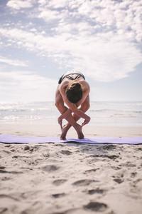 Sports woman doing yoga along the beach
