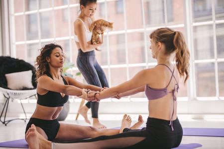 Women doing yoga in pair indoors