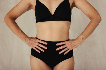 Unrecognizable aging female body wearing black underwear