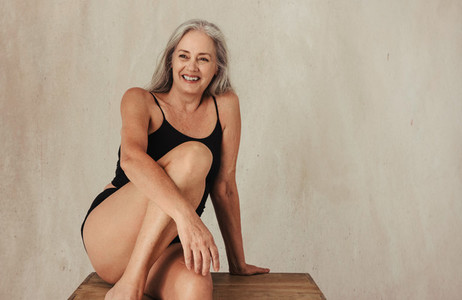 Smiling mature woman embracing her aging body