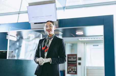 Airlines attendant with face shield standing at airport