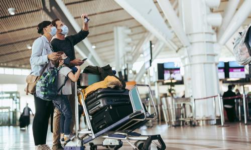 Family checking their flight timing at airport terminal