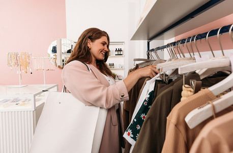 Female customer at fashion store  Smiling woman choosing clothes