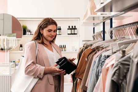Woman buyer holding a mini bag while shopping in a clothing store