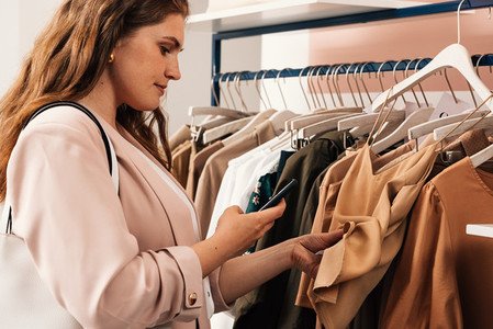 Side view of woman standing at a rack in clothing store scans the barcode using the mobile phone