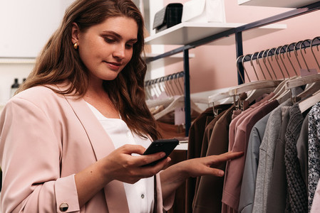 Plus size woman with a mobile phone standing at a rack in a small boutique