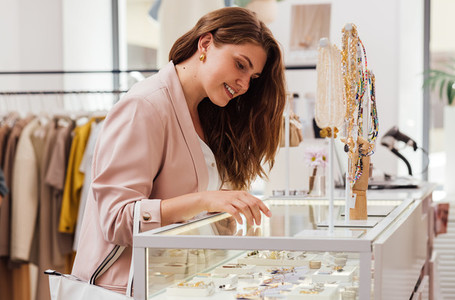 Side view of a beautiful smiling woman looking at display case in boutique