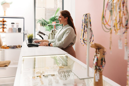 Side view of a small boutique owner working on laptop at counter