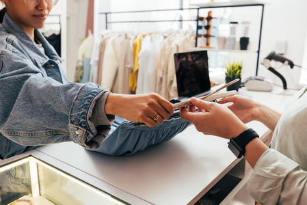 Female buyer giving clothes to unrecognizable clerk for checkout