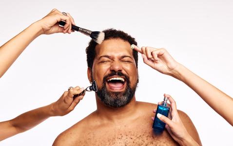Happy bearded man having facial grooming