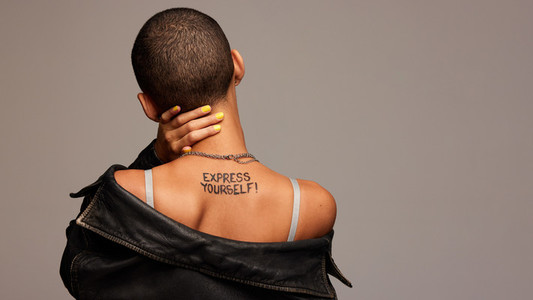 Androgynous woman with express yourself written on back