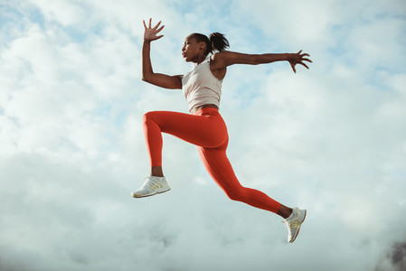 Woman running and jumping in midair against sky