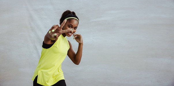 African sportswoman showing peace gesture using hand