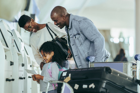 Family at airport checking boarding pass