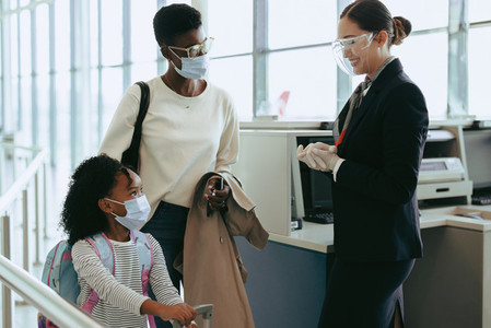 Family of two at airport traveling during pandemic