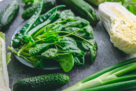 Green vegetables on a grey background   Squash  onion  spinach  cucumber  pepper and mint  Flat lay  top view
